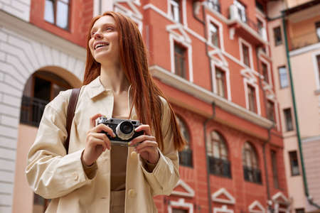 Caucasian redhead female tourist in beige coat standing on street of old city and shooting on camera, walking in historical places alone, enjoying solo trip. Portrait of cute lady with camera in hands