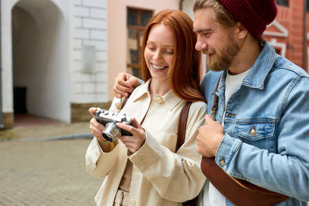 Positive caucasian couple tourists in casual clothes standing on street with photo camera during vacation in old city, looking at photo on screen of retro camera. side view portrait Standard-Bild