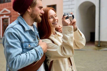 Process or taking pictures of old town by photographers travelers. Happy couple travel together. Side view portrait of smiling caucasian man and woman in casual outfit enjoying trip in new town Standard-Bild
