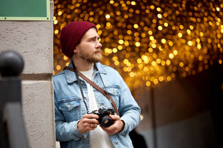 Caucasian hipster guy in denim jacket and red hat walk in city street taking photo, using film camera, Garlands lights in the background, copy space. Photography, people lifestyle concept. Standard-Bild