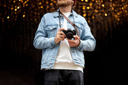 Portrait of cropped Hipster bearded man using retro film camera, making photos while walking in city. Urban background, garlands lights. Copy space