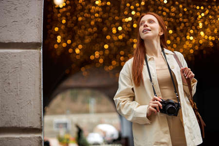 Pretty trendy young redhead woman with camera walk in city, boce garlands in the background. Portrait of beautiful lady in beige jacket enjoy walking alone outdoors. People lifestyle concept Standard-Bild