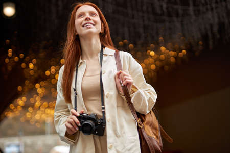 traveler woman stands outdoors in place decorated with lights, uses retro camera, walking and taking photo, looking happy. portrait of redhead caucasian female in beige jacket looking at side smiling