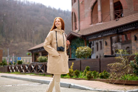 Young happy redhead traveler with long red hair walking under spring rain. Cheerful funny woman enjoying spring raindrops on rainy day outdoors. Spring season, bad weather and rain concept.