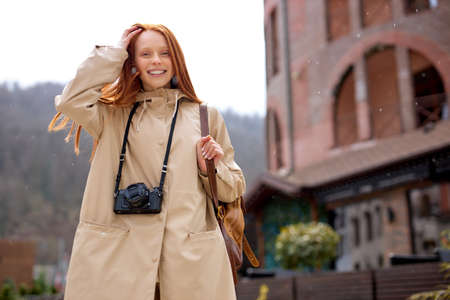Pretty young woman with long red straight hair wearing beige coat walking in town at rainy cold day. Smiling redhead female with retro film camera enjoying walk alone, mountains in the background
