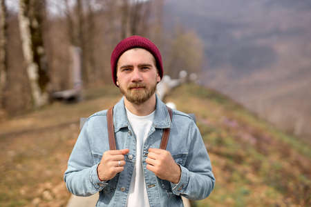 Traveler man with backpack walking alone in nature. Freedom concept. Copy space. Young caucasian bearded male in denim jacket enjoy landscapes. Travel, adventure, nature concept
