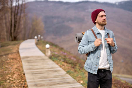 Young caucasian bearded man in nature, looking at side, enjoying the scenery, landscapes. Handsome guy in casual wear traveling alone, looking at interesting sights around him Standard-Bild