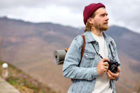 Handsome Caucasian man with backpack and camera is walking towards distant mountain. Bearded Man hiker hiking in mountains in spring. Traveler travels on country road, ecotourism, hiking.