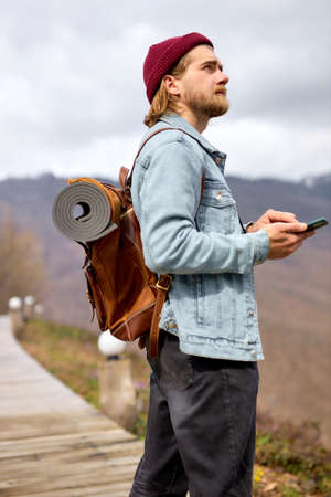 Side view portrait of handsome bearded man traveler with backpack using smartphone, mobile phone, checking online map while traveling, hiking. travel concept