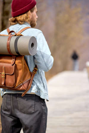 Man Walking Alone Camping Wanderlust Concept, Rear View On Guy In Casual Wear Traveling, In Casual Clothes, Alone. Travel, Hiking, Active Lifestyle, Adventure Concept. Focus On Leather Backpack