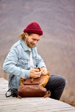 tourist man looking for things in leather brown backpack during hike in mountains, sit having rest, alone, side view portrait of handsome hipster guy in casual wear and hat. copy space