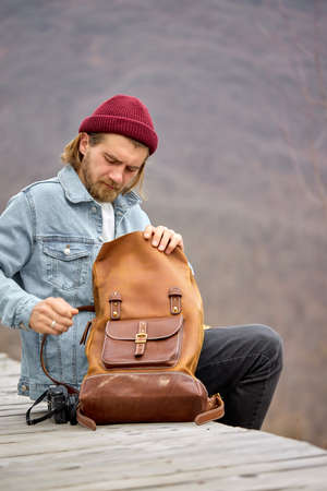 tourist man tourist man opening leather brown backpack during hike in mountains, sit having rest, alone, side view portrait of handsome hipster guy in casual wear and hat. copy space