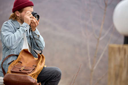 Young caucasian male travel with leather backpack on adventure taking photo on high mountain scenery, holding camera in hands, side view portrait. copy space