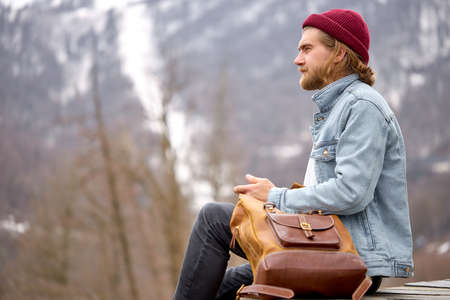 Stylish young caucasian man sit having rest in mountain landscape. tourist male with leather brown backpack, enjoy mountains nature. alone, outdoor portrait. hipster tourist in casual outfit Standard-Bild