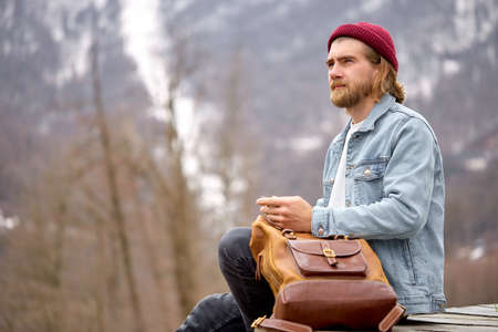 Side view on young caucasian man sit having rest in mountain landscape. tourist male with leather brown backpack, enjoy mountains nature. alone, outdoor portrait. hipster tourist in casual outfit