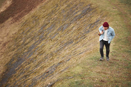 Hipster traveler in casual outfit walking in nature, climb the Hill, man walks confidently. Caucasian guy exploring new areas in countryside, tourist outdoors at spring weather Standard-Bild