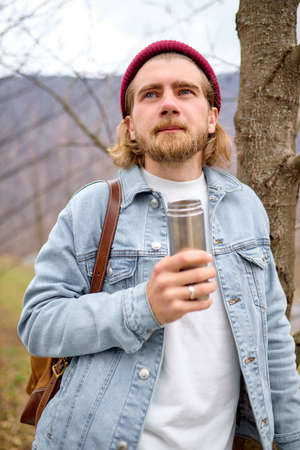 young handsome brutal bearded man traveling in the wild nature with , autumn or spring style, traveler in casual wear have rest, standing next to tree, adventure, free spirit