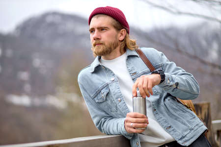 young handsome brutal bearded man traveling in the wild nature with , autumn or spring style, traveler in casual wear have rest, looking at side on landscapes, adventure, free spirit Standard-Bild