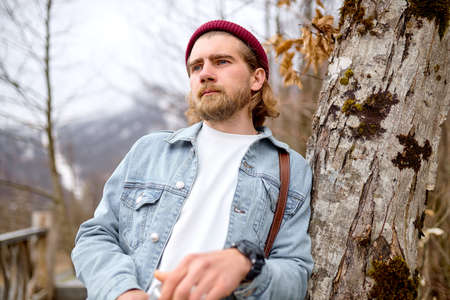 Upset handsome caucasian traveler in denim jacket near tree in spring weather, looking at side, thinking. Copy space. People lifestyle, human emotions, travel concept.