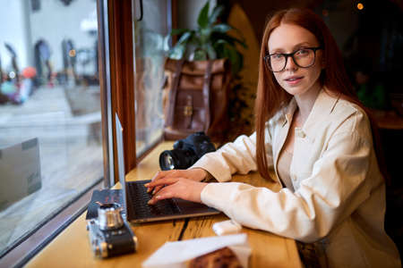 Confident redhead caucasian woman traveler using laptop computer in cafe, working at coffee shop, look at camera. freelance worker concept. Film color tone. Side view portrait. cozy atmosphere