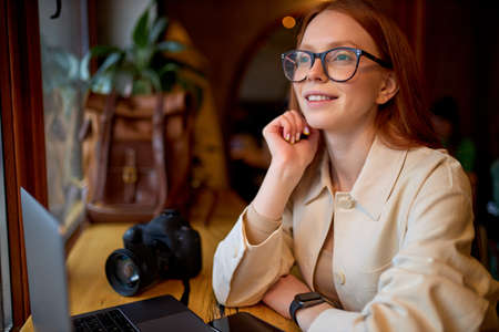Dreamy happy young female photographer in spectacles sitting with laptop and camera at cafe. Concept of modern technology and photoartist. Side view portrait. Caucasian redhead female on freelance