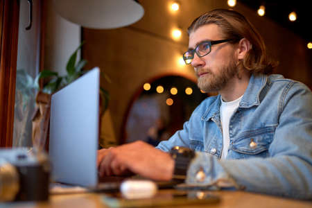 Bearded man sitting at cafeteria table with modern laptop, freelancer enjoying leisure for working remotely, in denim jacket, casual wear. copy space. concept of freelance and social networks Standard-Bild