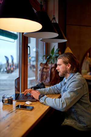 Portrait of concentrated bearded male photographer journalist sitting at cafe working with digital netbook computer, working remotely with media files. side view. copy space. freelance concept