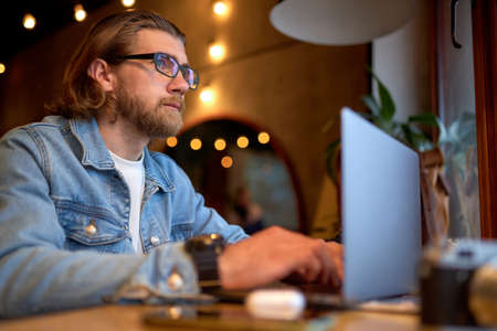Side View Portrait Of Handsome Caucasian Guy In Denim Jacket Working On Laptop, Focused On Work, Side View portrait. Hipster Man Enjoy Working On Freelance, Thinking