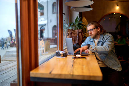 Young successful bearded man sitting at cafe and surfing internet on laptop. Concept of freelance and social networks. copy space. people lifestyle concept