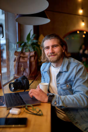 Portrait of positive bearded guy looking at camera while working on laptop in cafe, looking pleasant and nice, wearing denim jacket, casual outfit. camera on table. copy space
