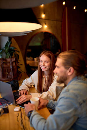 Side view portrait of cheerful caucasian managers photographers redhead female and bearded guy working in cafe, use laptop, surfing internet, having talk, copy space. freelance concept Standard-Bild