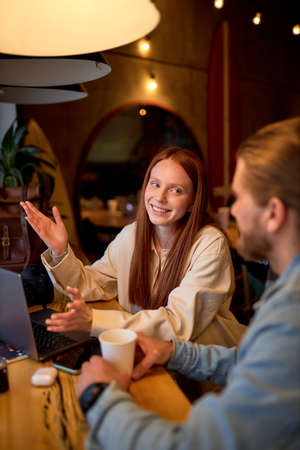 Handsome Man and positive redhead woman discussing business projects in cafe while having coffee. In Cozy cafeteria. Startup, ideas and brain storm concept. Side view. COpy space Standard-Bild