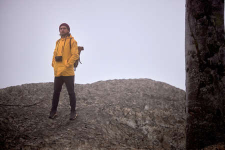 Handsome traveler Male with camera walking down the mountain, at foggy weather, alone , in yellow coat, stands looking at side, in wild nature, adventure, hiking concept
