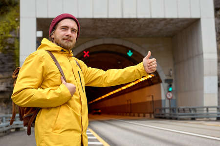 Portrait of young man hitchhiking around the country, trying to catch passing car for traveling. Caucasian hipster man in yellow coat with backpack went hitchhiking to south. Standard-Bild