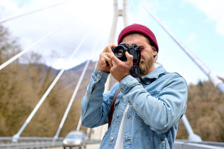 Handsome caucasian male in denim jacketwalking on bridge in countryside using camera, stand outdoors taking photo, in casual denim jacket, hat. portrait, copy space