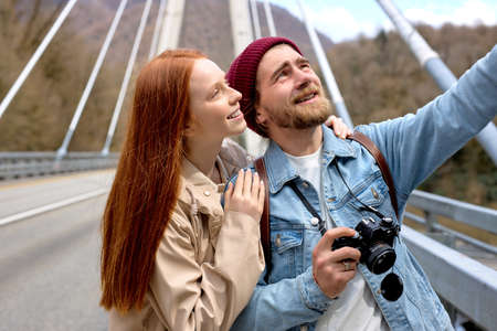 Portrait of caucasian man and woman in casual wear walking on bridge, in contemplation of mountains, landscapes around. Handsome male pointing finger at side, showing something to girlfriend