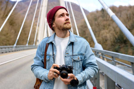 Hipster male in denim jacketwalking on bridge in countryside using camera, stand outdoors taking photo, in casual denim jacket, hat. portrait, copy space
