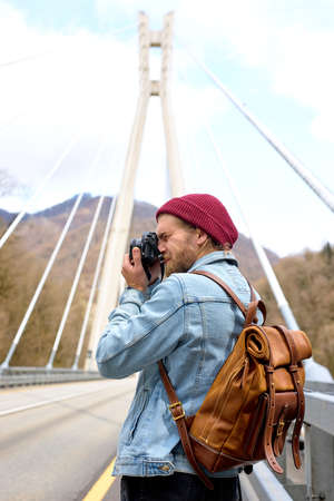 Handsome hipster caucasian guy walking on bridge in urban area taking photo on camera, wearing denim jacket, looking at side, alone outdoors. travel, adventure, vacation concept