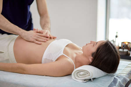 Male hands of massage therapist making light massage to the belly of pregnant female in cosmetology room, in spa or wellness center indoors. Side view Standard-Bild