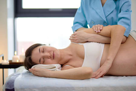 Beautiful pregnant gravid brunette woman enjoying back and shoulders massage in beautician room in spa center, side view on relaxed lady lying on bed with eyes closed, having rest