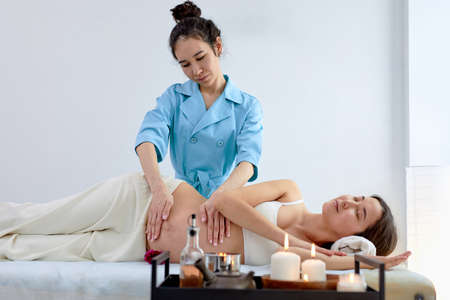 Pregnant asian young woman lying on bed and having relaxing oriental prenatal massage on belly, enjoying professional massage, preparing for giving birth, training muscles