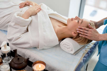 Unrecognizable female masseur in blue wear doing relaxing massage to client woman lying on couch, caucasian lady is relaxed, enjoying spa treatment in beauty salon, in room with candles