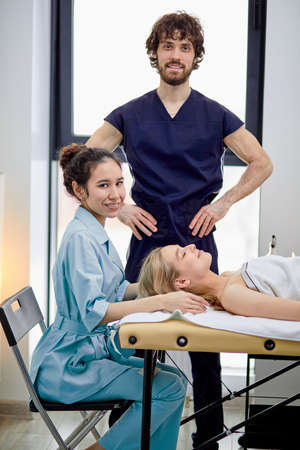 Two pleasant masseurs practice massaging on female client face and head, male and female masseur in uniform work together, blonde lady lying on massage couch, relaxed. copy space
