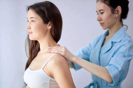 Brunette Expectant Woman Getting Neck and Shoulders Massage by Female Masseur. Professional skin care at wellness center. Relaxation, beauty, spa treatment concept, copy space, female looking at side Standard-Bild