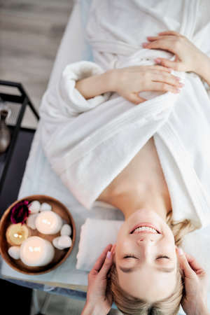 Top view of positive caucasian woman relaxing while careful specialist massaging her face, adorable blonde lady in white bathrobe lying on couch enjoying spa procedure, with eyes closed
