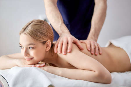 Gorgeous lady lying on tummy receiving massage on back by cropped male therapist, caucasian guy in blue uniform carefully massaging back muscles of client. copy space