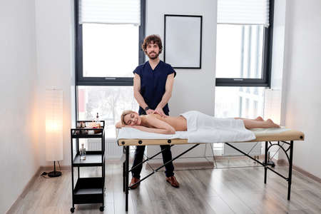 Portrait Of Bearded Nice Masseur In Uniform Carefully Doing Massage On Female Back, Blonde Caucasian Woman Lying On Belly Relaxing, Enjoying. Copy Space For Advertisement