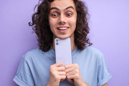 Close-up portrait of cheerful smiling guy taking photo on smartphone, holding mobile phone closely to himself, curly male enjoys free time, have fun