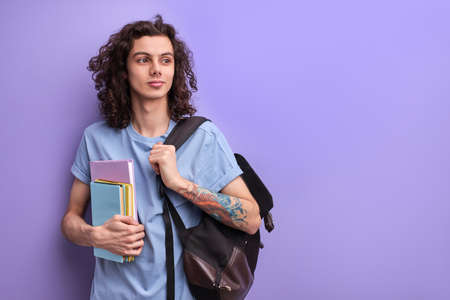 Young Caucasian Guy Is Ready For Getting Knowledge In College Or University, Looking At Side, With Bagpack and Books In Hands Standard-Bild