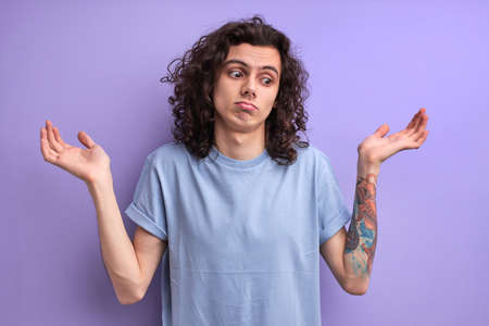 I dont know. Portrait of confused handsome young male in blue casual t-shirt standing with raised arms and looking at side with answer. indoor studio shot, isolated on purple background.